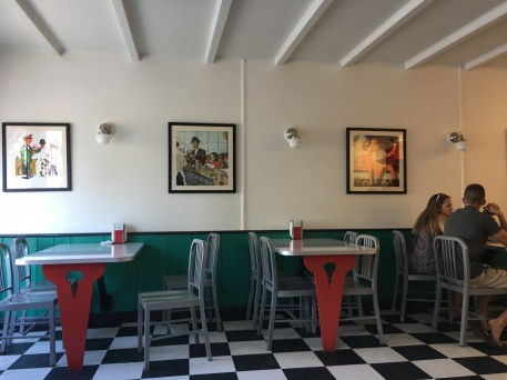 Two 50s style tables and Norman Rockwell paintings near an ice crema bar